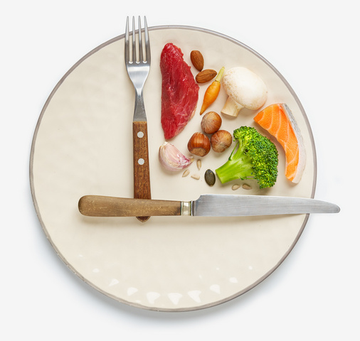 20:4 fasting diet concept. One-third plate with healthy food and the two-third plate is empty. Beef, salmon, egg, broccoli, tomato, nuts, carrots, mushrooms, cucumber, dates.